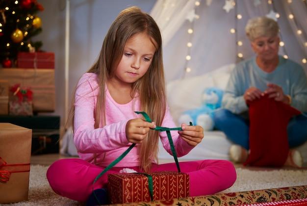 Chica empaquetando un regalo de navidad