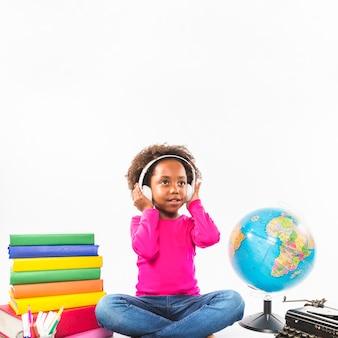 Chica en auriculares cerca de libros y globo en estudio