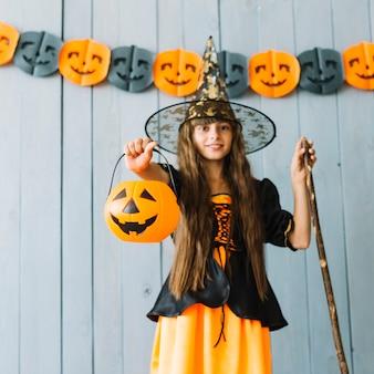 Chica en traje de bruja con cesta de halloween
