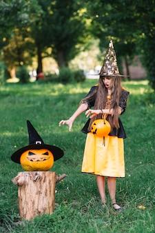 Chica en traje de bruja mostrando llegar manos en calabaza