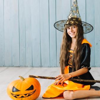 Chica en traje de bruja y sombrero puntiagudo sentado en el piso y sonriendo