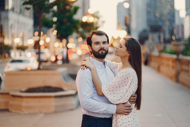 Chica en traje de verano con su guapo esposo en camisa blanca y pantalón