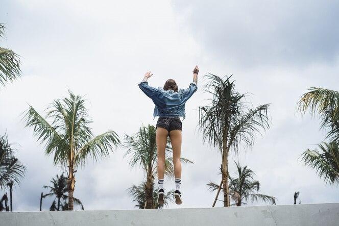 Chica en una chaqueta de mezclilla en un lugar tropical