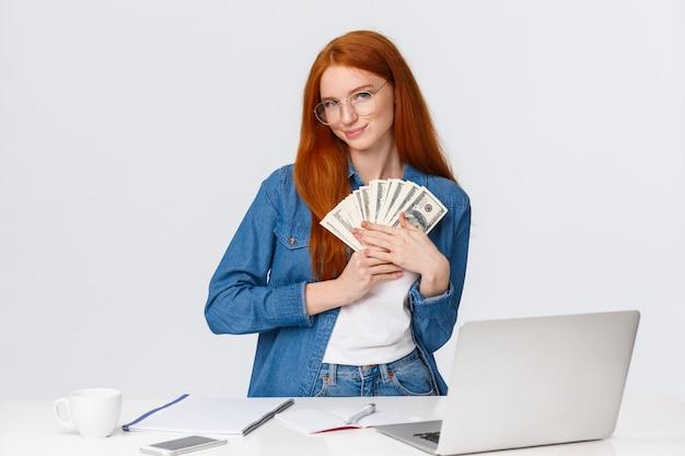 A la chica le encanta el dinero, siente el calor del dinero en efectivo en las manos, se queda tonta y encantada, recibe un sueldo y sonríe, va de compras en línea, hace pedidos por internet, está de pie cerca de una computadora portátil, pared blanca