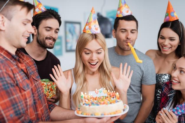 Chica está encantada con un pastel con velas para cumpleaños.