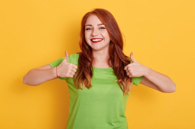 Chica encantadora alegre mostrando los pulgares para arriba mientras posa aislada, chica pelirroja en camiseta verde