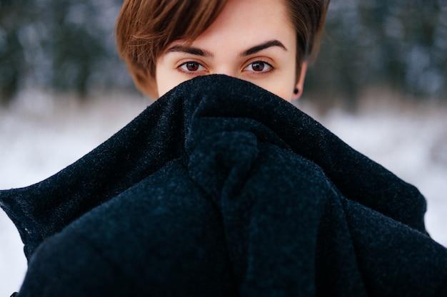 Chica encantadora con bello rostro angelical. mujer rizada en invierno bosque nevado congelación y cubierta con ropa de abrigo. señora emocional ojos mirando.
