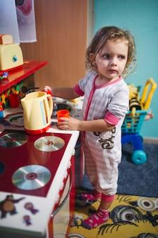 Chica encantadora cerca de cocina de juguete