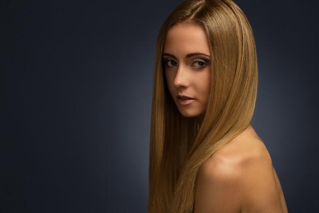 Chica encantadora desnuda teniendo una sesión de fotos en un estudio