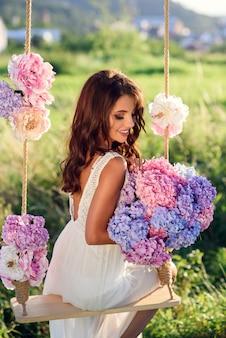 Una chica encantadora con una hermosa sonrisa en un vestido blanco sentado en un columpio de madera con flores al atardecer.