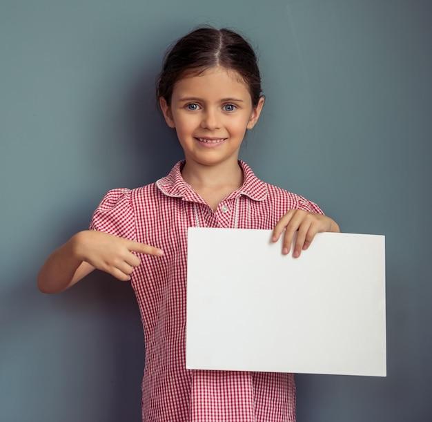 Chica encantadora en lindo vestido está sosteniendo una hoja de papel en blanco