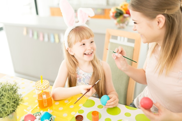 Chica encantadora con madre pintando huevos
