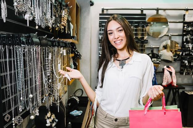 Chica encantadora posando en tienda de accesorios