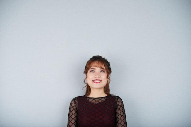Chica encantadora recortada mirando hacia arriba sonriendo de pie en la pared gris