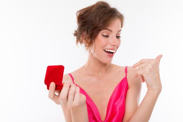 Chica encantadora en un vestido rosa trata de anillo en dedo anular sosteniendo una caja en blanco
