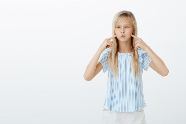 Chica enfurruñada, con aspecto de globo. retrato de linda joven hija rubia infantil en elegante blusa azul, haciendo pucheros y señalando las mejillas, siendo desobediente y aburrida, de pie sobre una pared gris