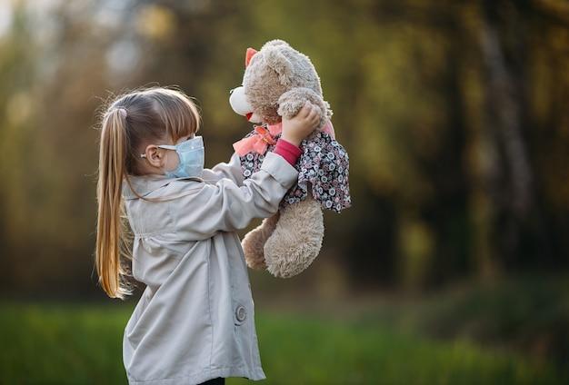 Chica enmascarada sosteniendo un oso en el parque.