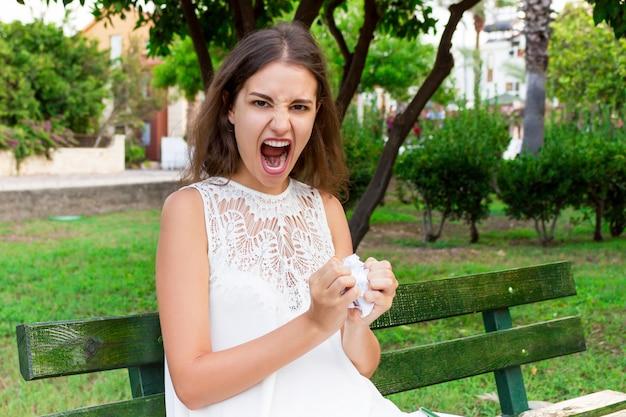 Chica enojada y molesta sostiene papel arrugado