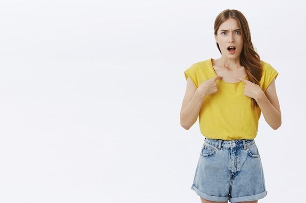 Chica enojada ofendida apuntando a sí misma, lidiando con la ofensa