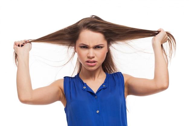 Chica enojada sostiene su cabello en las manos