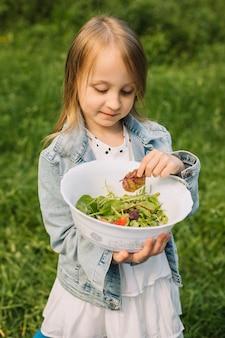Chica con una ensalada en la naturaleza