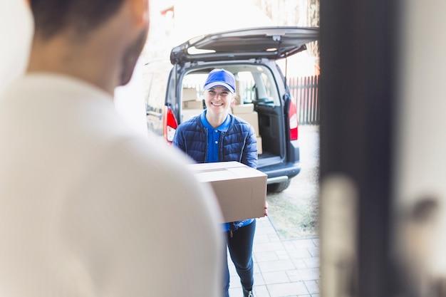 Chica de entrega que lleva la caja al cliente