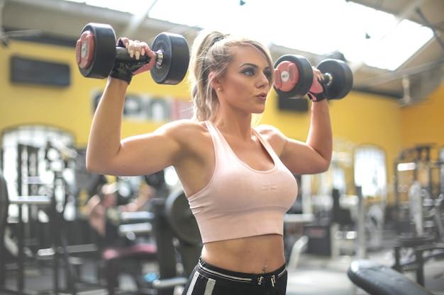 Chica entrenando con pesas en el gimnasio