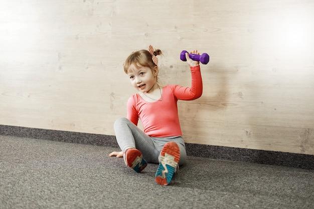 Chica está entrenando con pesas en el gimnasio.