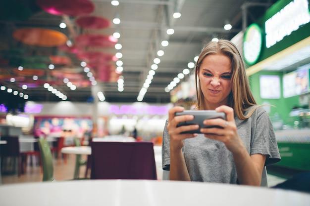 Chica enviando mensajes de texto en el teléfono inteligente en un restaurante