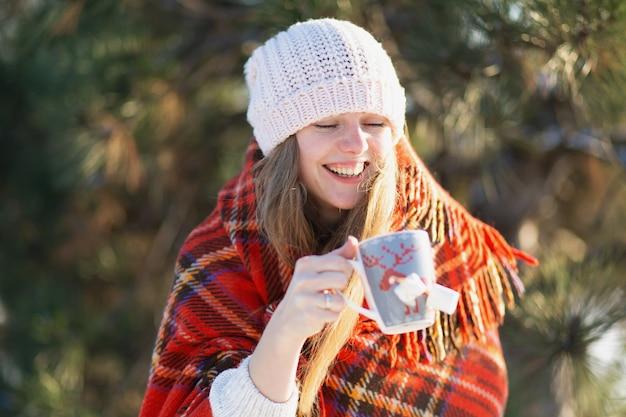 Chica envuelta en una cálida tela escocesa bebe café de invierno con malvaviscos en la calle