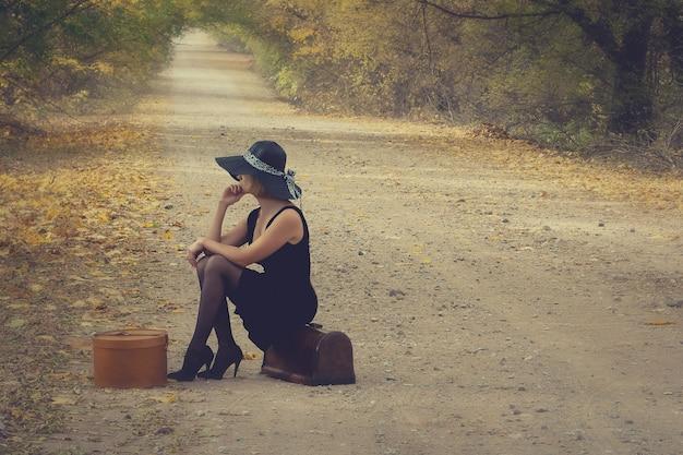 Chica con equipaje en estilo vintage