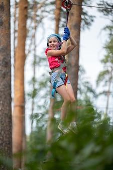 Chica en equipo supera un obstáculo en un parque de cuerdas a una altura