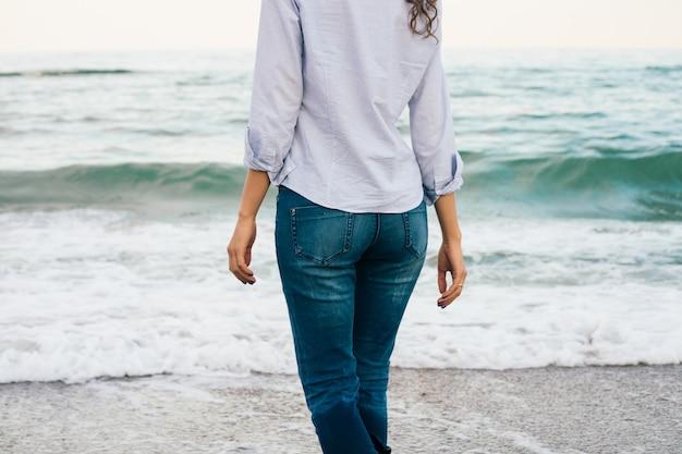 Chica esbelta en camisa y jeans caminando por la playa. vista desde la parte posterior