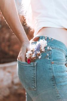 Una chica esbelta se encuentra de espaldas con jeans azules y flores en el bolsillo trasero.