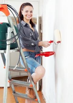 Chica en escalera de mano pinta pared con rodillo