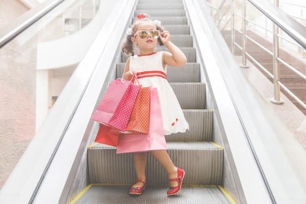 Chica en la escalera mecánica en el centro comercial con compras