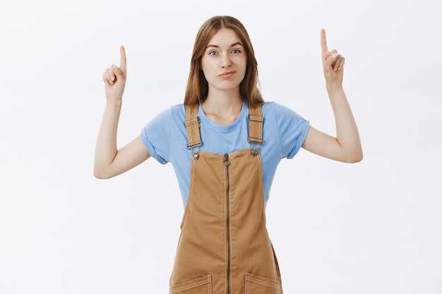 Chica escéptica y disgustada apuntando con el dedo hacia el logotipo o anuncio