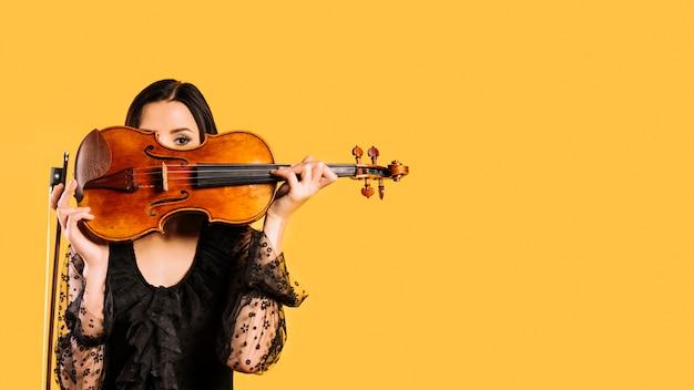 Chica escondiéndose tras el violín