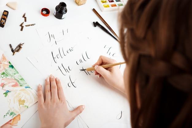 Chica escribiendo caligrafía en postales. diseño artístico.