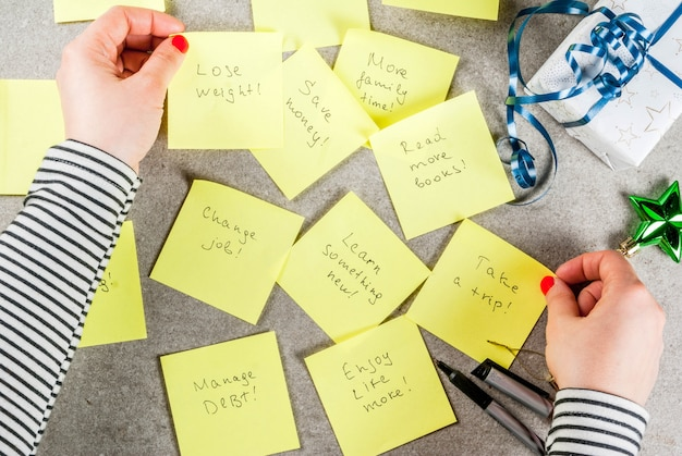 Chica escribiendo resoluciones de año nuevo con las manos en la mesa mesa de piedra gris con coloridas notas adhesivas con populares resoluciones de año nuevo y bolígrafo