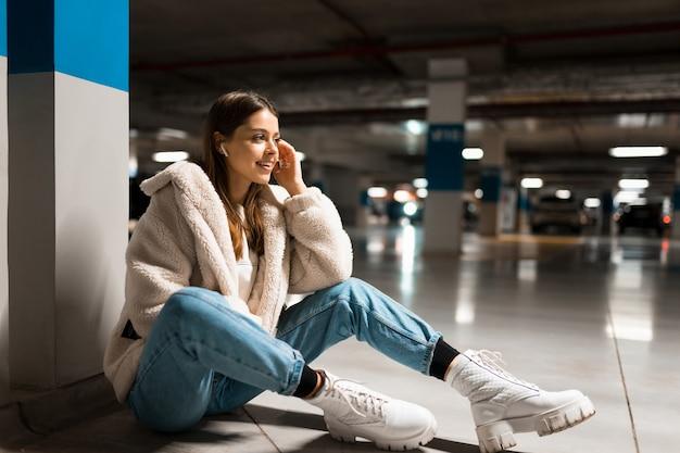 Chica escucha música en el centro comercial
