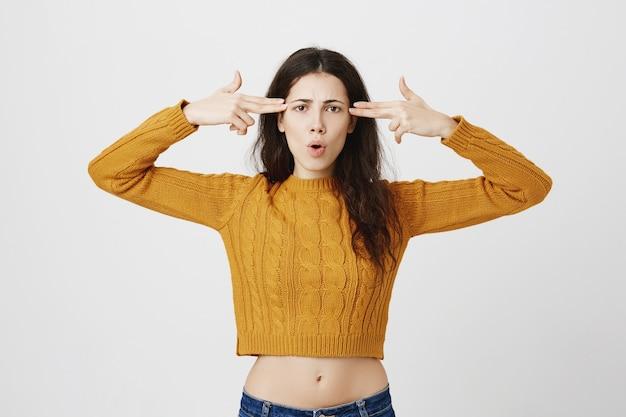 Chica escucha noticias alucinantes, hace gestos de armas de mano sobre la cabeza