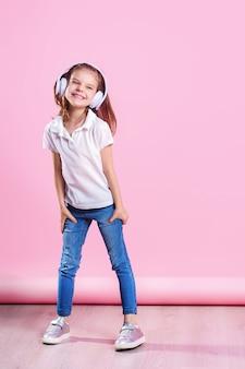 Chica escuchando música en auriculares un baile en la pared rosa.