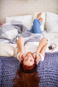 Chica escuchando música en auriculares en la cama. dormitorio brillante luz de la mañana desde las ventanas