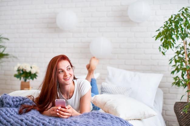 Chica escuchando música en auriculares en la cama.