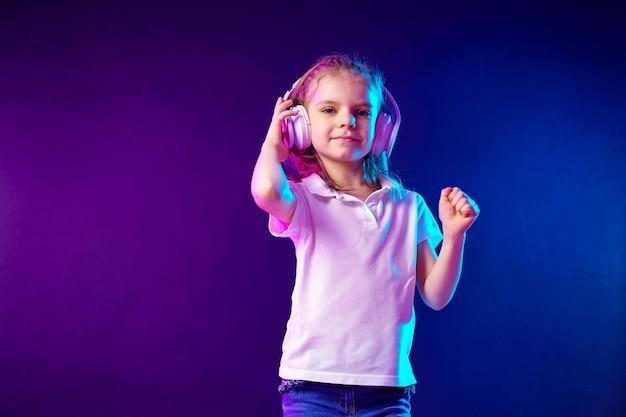Chica escuchando música en auriculares. niño lindo que disfruta de música de baile feliz, mirando y sonriendo posando