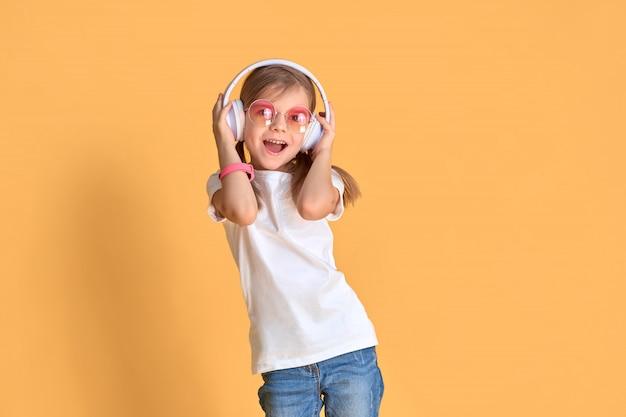Chica escuchando música en auriculares. niño lindo que disfruta de música de baile feliz