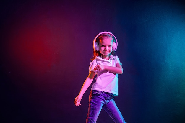 Chica escuchando música en auriculares en la pared colorida oscura. luz de neón. bailarina. niña feliz bailando con música. niño lindo que disfruta de música de baile feliz.