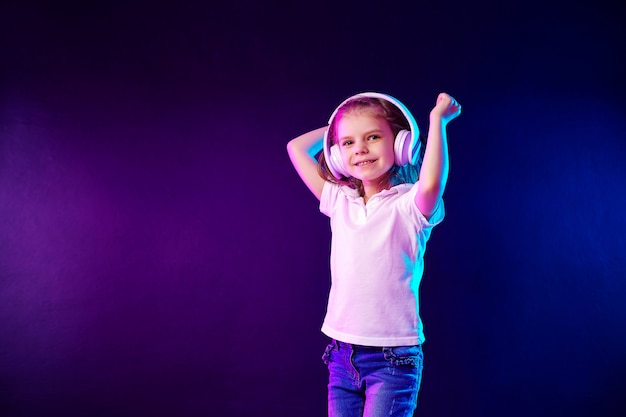 Chica escuchando música en auriculares en la pared colorida oscura. niño lindo que disfruta de música de baile,
