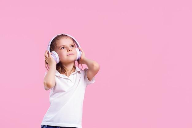 Chica escuchando música en auriculares en pared rosa.